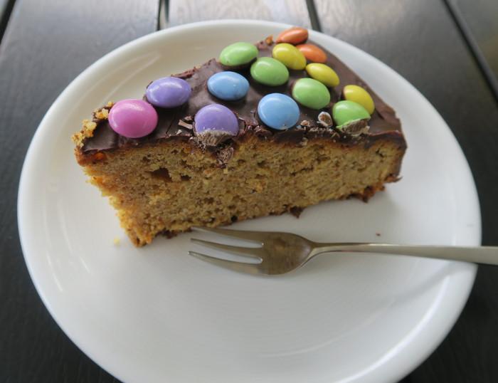 Ein Stück eines Rüebli Smarties Kuchen