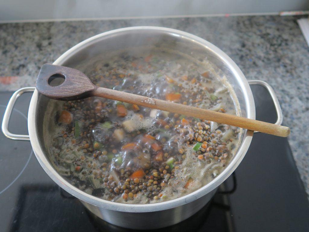 Zutaten für Linsensuppe in einen Topf geben und mit Wasser bedecken und köcheln lassen.
